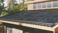 Domestic roof covered with black solar pool heater.